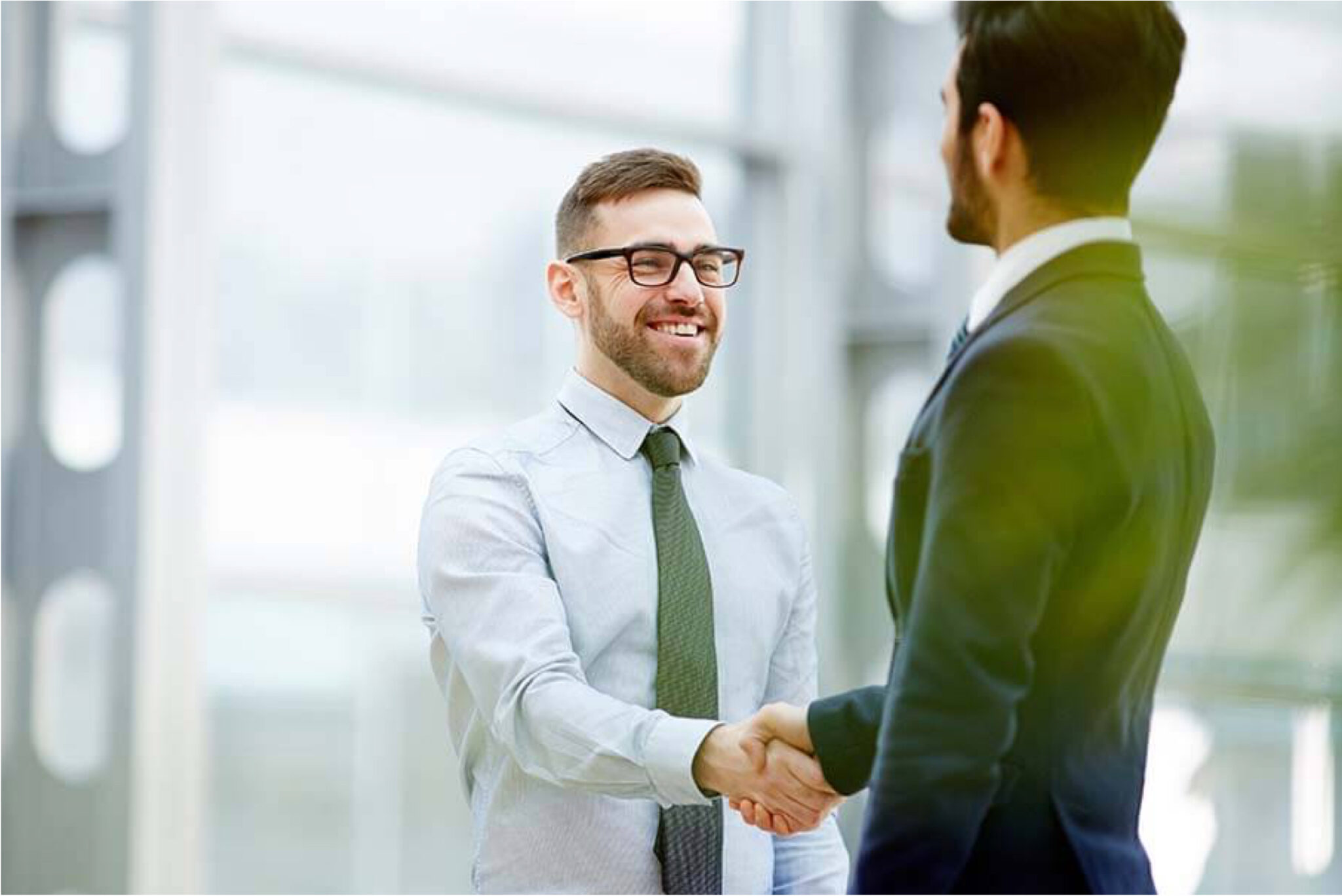 Two men in suits shaking hands.=