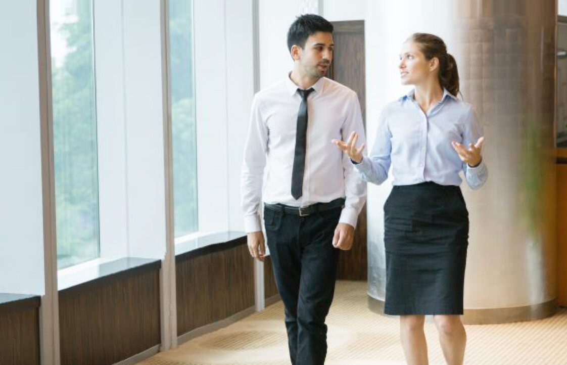 A woman in a black pencil skirt talks with her hands while walking down the hallway with a male colleague
