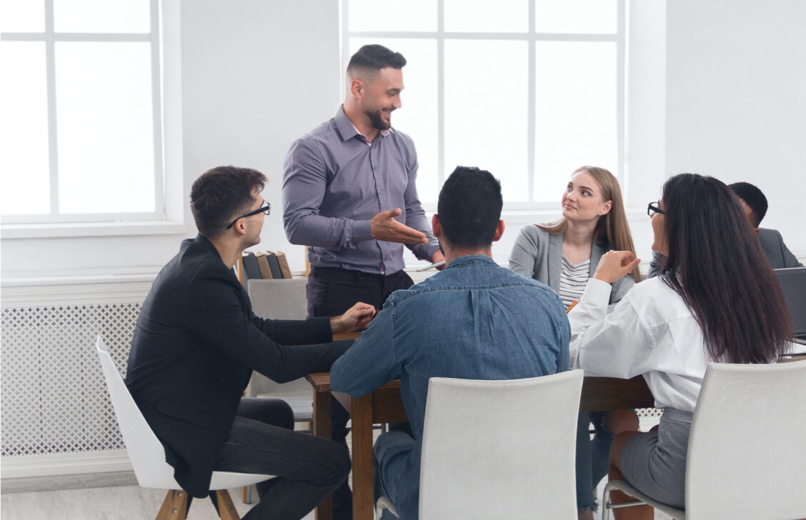 A man is standing up during a business meeting